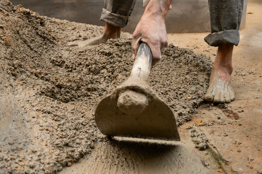 Indian labour mixing cement using shovel.