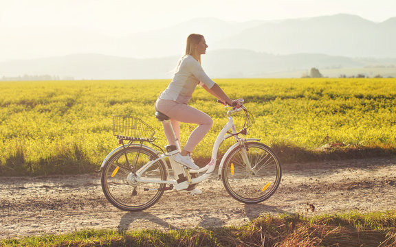 Young woman rides electric bicycle on dusty country road, view from side, sun backlight field with yellow flowers background