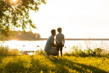 Father and his little son. Happy loving family walking outdoor in the light of sunset.