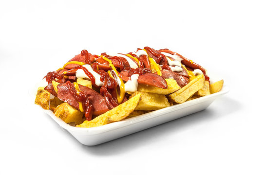 Peruvian street food:  Classic salchipapas or sausages and french fries  with ketchup, mustard, mayonnaise and chili peppers served on a white plate