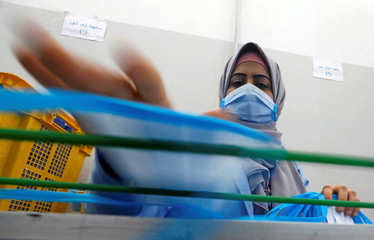 A woman wearing a protective face mask works at a factory that produces sterilised surgical equipment and medical clothings in Egypt