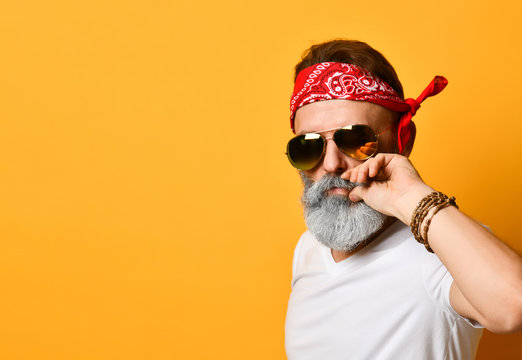 Grandpa in sunglasses, red bandana, white t-shirt and bracelet. He straightens his mustache, posing on orange background