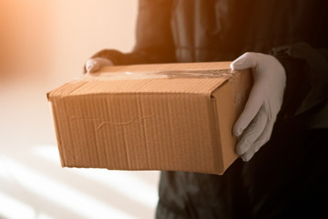girl courier holds a parcel in protective gloves. epidemic. close-up. sunlight