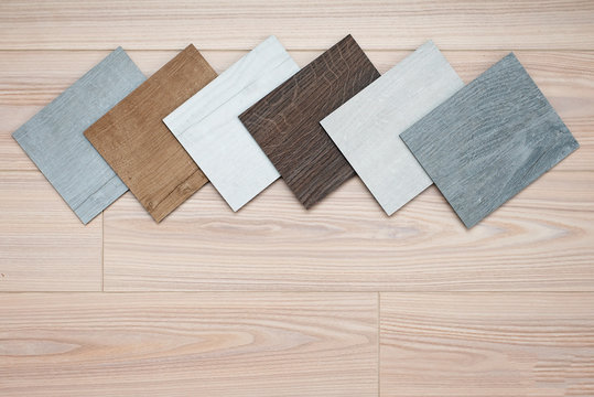 Sample catalog of luxury vinyl floor tiles with a new interior design for a house or floor on a light wooden background.