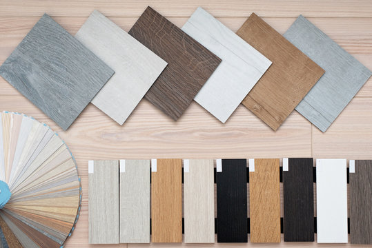 An example of a catalog of luxury vinyl floor tiles and a designer palette with textures with a new interior design for a house or floor on a light wooden background.
