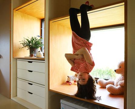 Ein Mädchen hängt während der Coronakrise gelangweilt kopfüber am Fenster am 01.04.2020.