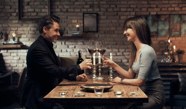Cheerful couple drinking wine and having romantic dinner at home. Home date night, clinking wine glasses.