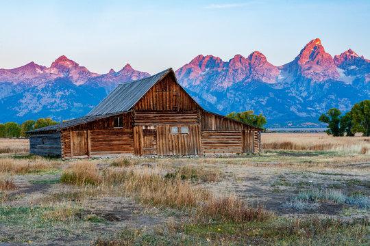 Historic mormon barn in front of the Grand Tetons at sunrise, Grand Teton National Park, Wyoming.
