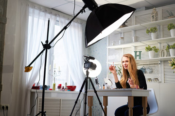 Beauty blogger woman filming daily make-up routine tutorial on camera. Influencer blonde girl live streaming cosmetics product review in home studio with professional lighting equipment. Vlogger job. Fototapete