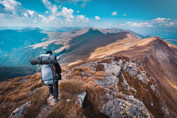 Aluminium Prints Blue sky Hiking trough epic mountain landscape with a big backpack, exploring and feeling the freedom of nature