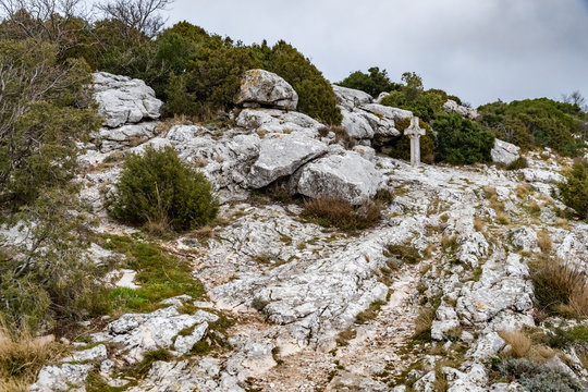The sacred cross St.Pilon is on the mountain in cloudy weather, clouds over a valley, a dry grass, mountain over grotto of Mary Magdalene