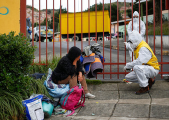 A city official talks to a migrant woman who had spent the night on the street, outside a sports stadium turned into a shelter for homeless Venezuelan migrants, as the country is under a nationwide quarantine to contain the coronavirus disease (COVID-19),