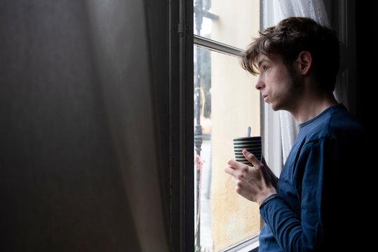 man in pyjamas looking through the window during quarentine
