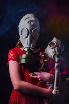 social distancing young girl hugging doll wearing gas mask in smoke filled virus room