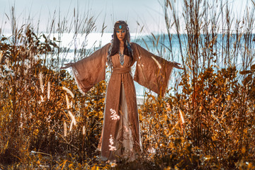 beautiful young woman in tribal costume outdoors at sunset