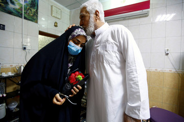 Farah Al-Awadi, a 28-year-old Iraqi woman who left quarantine after her recovery from coronavirus disease (COVID-19), wears a protective mask is seen while her father kisses her at her home in the holy city of Najaf