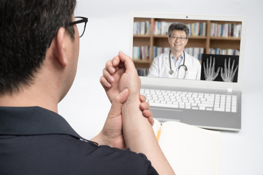 An Asian middle-aged man using a laptop to consult a doctor on telemedicine.