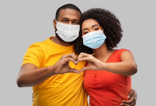 health, quarantine and pandemic concept - happy african american couple wearing protective medical masks for protection from virus making hand heart gesture over grey background