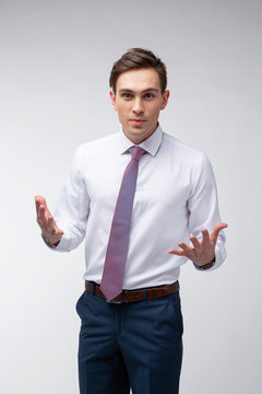 Young, handsome man in a white shirt with a tie on a white background in studio