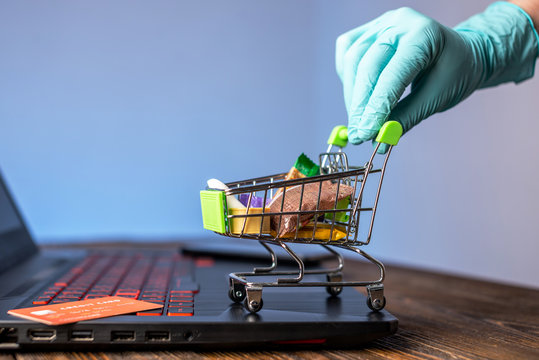 Hand in a sterile glove holds a shopping cart with a credit card. Internet purchasing during the coronavirus pandemic