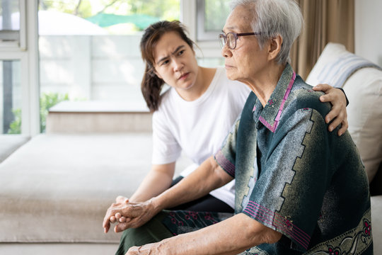 Caregiver woman is taking care,support of sad senior, depressed elderly looking away outside waiting for her family to visit at nursing home, nostalgia, stressed, anxious,life depression of old people