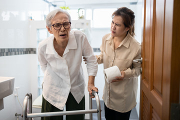 Asian senior woman hand holding her bottom suffer from hemorrhoids,anal fissure,anal pain,constipation in toilet,elderly having abdominal pain,diarrhea or food poisoning,symptom of colorectal cancer