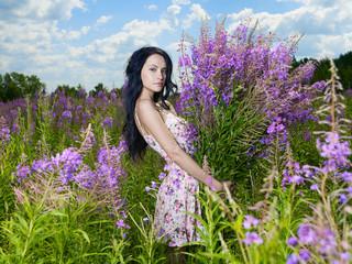 Papiers peints womenART Young beautiful girl picks flowers in the field.