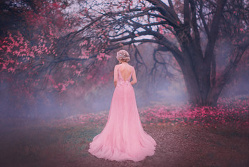 Mysterious silhouette princess. young blonde woman queen turned away. backdrop autumn nature mystic blue fog pink full bloom fairy tree black trunk. spring pink long elegant vintage dress bare back Wall mural