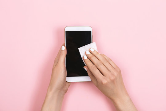 A woman disinfects smartphone screen. Protect yourself from bacteria and dirt. Keep your gadjets clean.