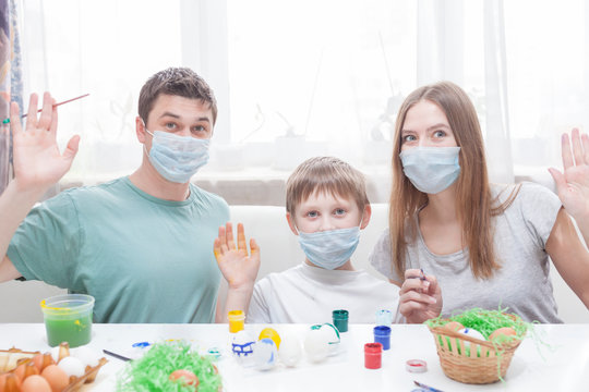 Dad, mom and child at the table in medical masks are painting Easter eggs for the holiday. Happy easter family quarantined coronavirus. Happy at home.