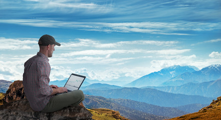man working remotely outdoors with laptop Fotomurales