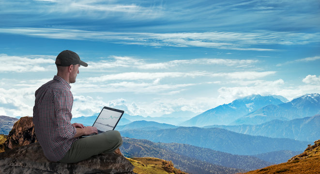 man working remotely outdoors with laptop