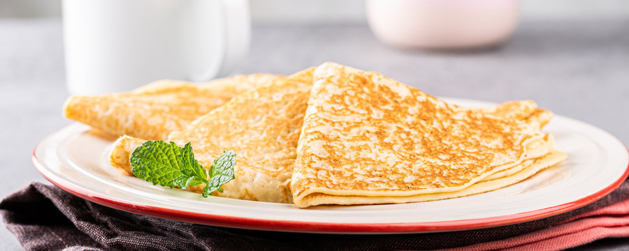 Delicious Tasty Homemade crepes or pancakes with honey, honey and mint on white plate. Healthy breakfast concept, gluten free. Banner.