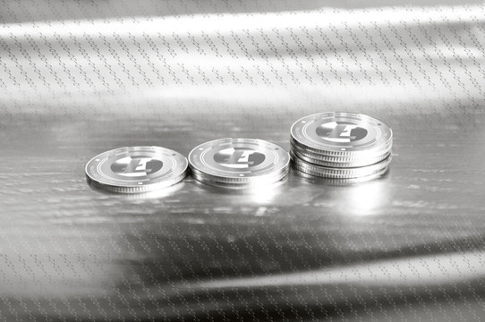 Litecoin (LTC) digital crypto currency. Stack of silver coins against the background of numbers. Cyber money.