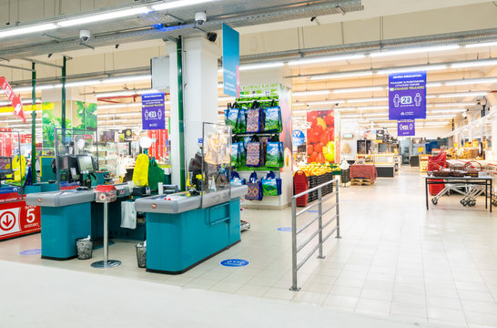 Cash desks with protective transparent shields in shop facility of Carrefour with no people around. New safety rules and changes in food industry concept.01.04.2020