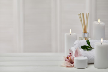 Spa products with aromatic candles, orchid flower and towel on white wooden table. Beauty spa...