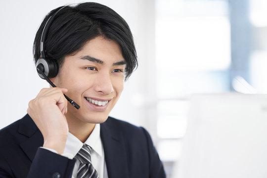コールセンターで話をする日本人男性スタッフ