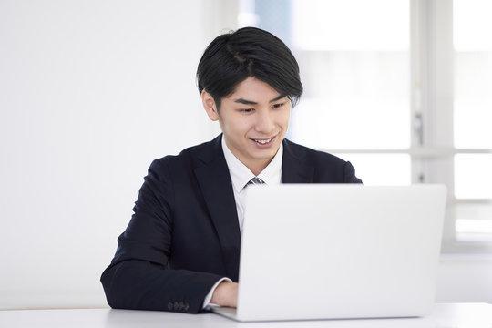 笑顔で自宅でスーツを着てテレワークをする日本人男性ビジネスマン