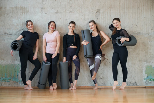 Group of five women holding mats after training.