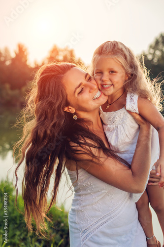 Mothers day. Happy woman playing and having fun with little daughter in spring park holding kid and laughing. Family