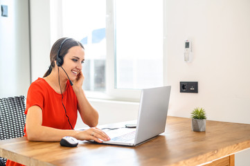 Young woman works from home using headset, laptop