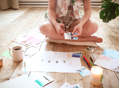 Young brunette woman creating her Feng Shui wish map using scissors