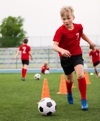 Soccer Boy on Training with Ball and Soccer Cones. Dribbling Drill. Soccer Kids Dribble Training. Youth Soccer Club Practice Session. Boys in Sports Team in Red Soccer Uniforms