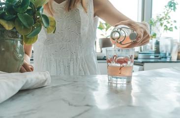 Woman pouring glass of kombucha