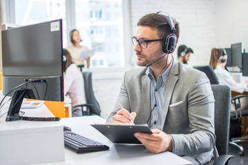 Handsome businessman checking data from computer and writing it to clipboard.