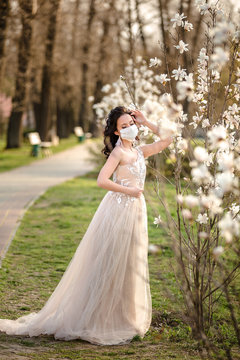 Bride dress and in a wedding medical mask near a blossoming magnolia. corona virus. Kovid-19 protects.
