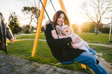 Family at the park at sunset plays on the swing for children - Copy space - Mother, father and child girl have fun together