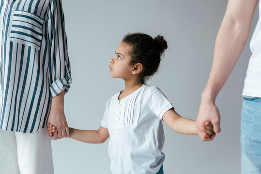 sad african american kid holding hands with divorced foster parents isolated on grey