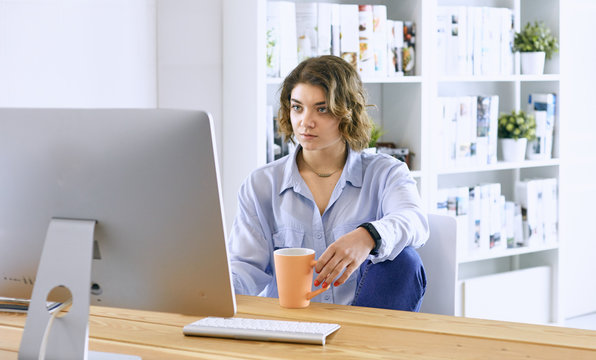 Young woman working with graphic tablet in office