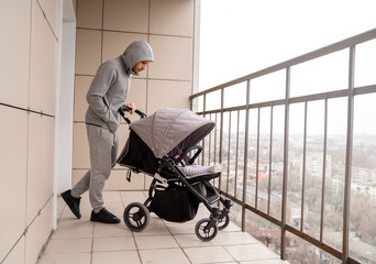 A man with a pram walks on the balcony of his apartment building. Concept Quarantine and self-isolation with children. Fresh air and health.